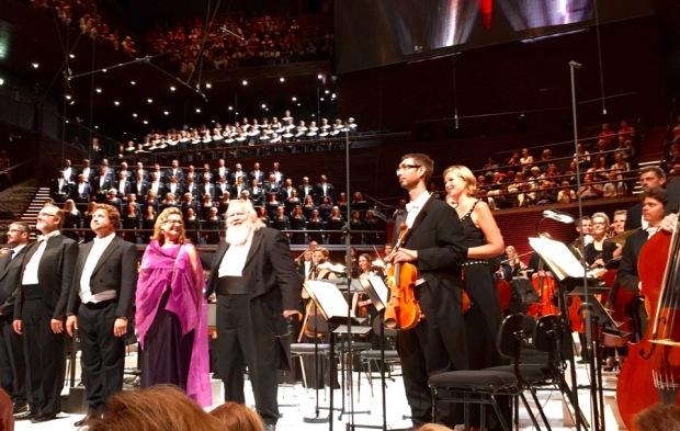 Loppuaplodeja vastaanottamassa keskellä Leif Segerstam, hänestä vasmalle Calire Rutter, Jeremy Ovenden, Stephen Gadd; heidän takanaan Oopperan kuoro ja ylempänä Cantores Minores